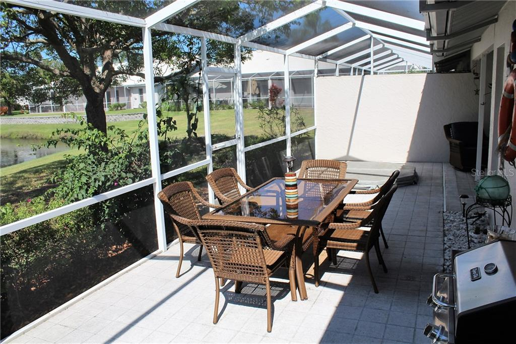 This sun-drenched screen-topped porch extends beyond the covered lanai.  Note the built-in hot-tub on the other side of the patio table and the shady oak between the patio and pond. - Villa for sale at 5438 Kelly Dr #12, Sarasota, FL 34233 - MLS Number is A4400319