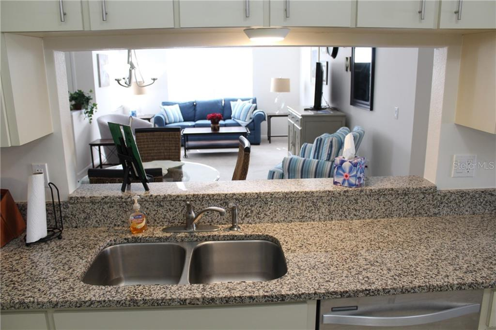 Pass-through from kitchen to dining area. Note under-mounted stainless sink. - Villa for sale at 5438 Kelly Dr #12, Sarasota, FL 34233 - MLS Number is A4400319
