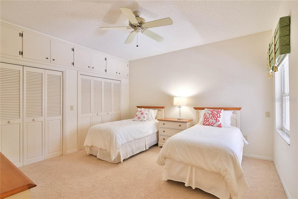 Second bedroom with a full wall of storage both below and above. - Villa for sale at 7686 Calle Facil, Sarasota, FL 34238 - MLS Number is A4413755