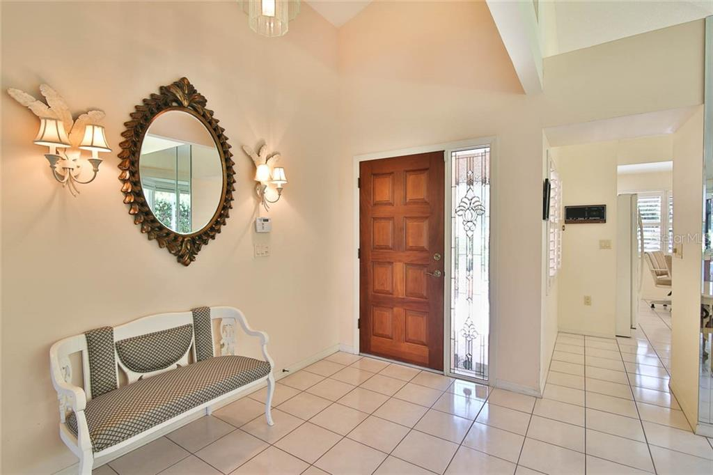 Foyer area, the kitchen entry is to the right. - Villa for sale at 7686 Calle Facil, Sarasota, FL 34238 - MLS Number is A4413755
