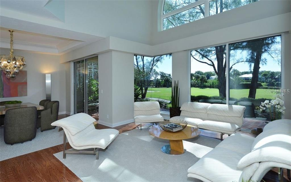 The living room looks out to the golf course and canal beyond - Single Family Home for sale at 3529 Fair Oaks Ln, Longboat Key, FL 34228 - MLS Number is A4414992
