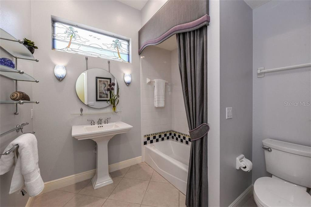 Roomy Guest Bath with Pedestal Sink, Glass Shelves & Sconce Lights - Single Family Home for sale at 7060 Whitemarsh Cir, Lakewood Ranch, FL 34202 - MLS Number is A4417363