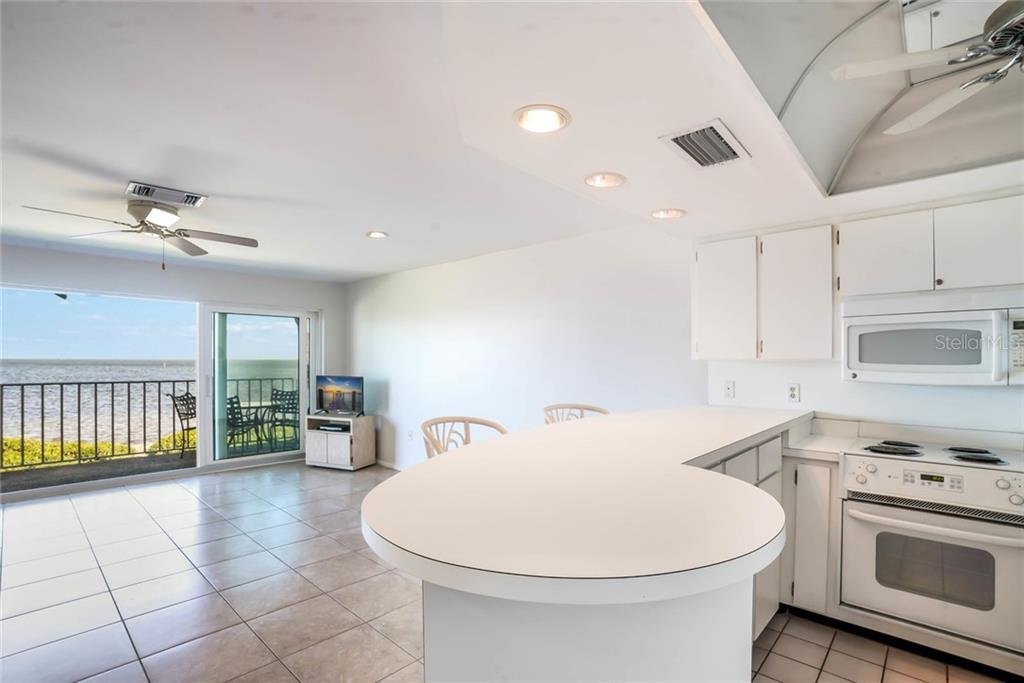 Imagine prepping your meal with that view and then simply walking out to your balcony to dine with bay breezes and soaring seabirds as your guests. - Condo for sale at 600 Manatee Ave #202, Holmes Beach, FL 34217 - MLS Number is A4419465