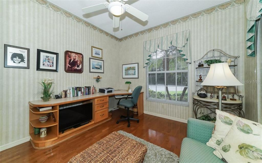 Office or guest room with hardwood floors & ceiling fan. - Single Family Home for sale at 6125 Varedo Ct, Sarasota, FL 34243 - MLS Number is A4420656