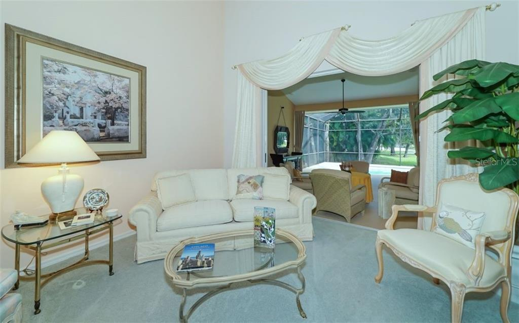 Formal Living room with sliding glass doors that pocket away & open to an expansive lanai. - Single Family Home for sale at 6125 Varedo Ct, Sarasota, FL 34243 - MLS Number is A4420656