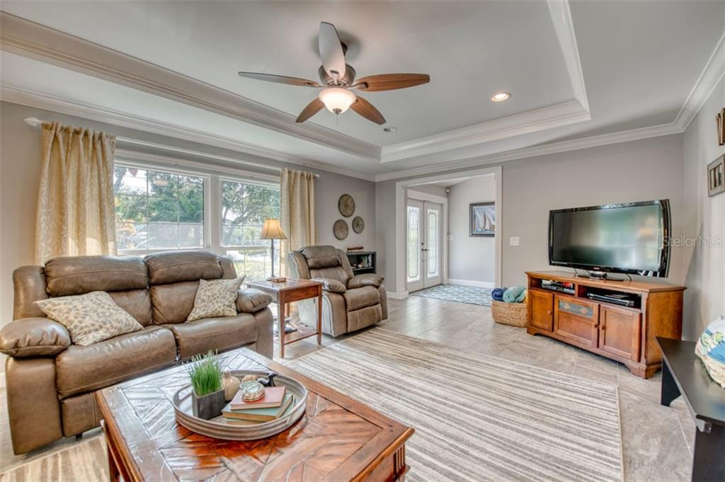 Living Room area with tray ceiling, new tile flooring - Single Family Home for sale at 5548 Shadow Lawn Dr, Sarasota, FL 34242 - MLS Number is A4423461