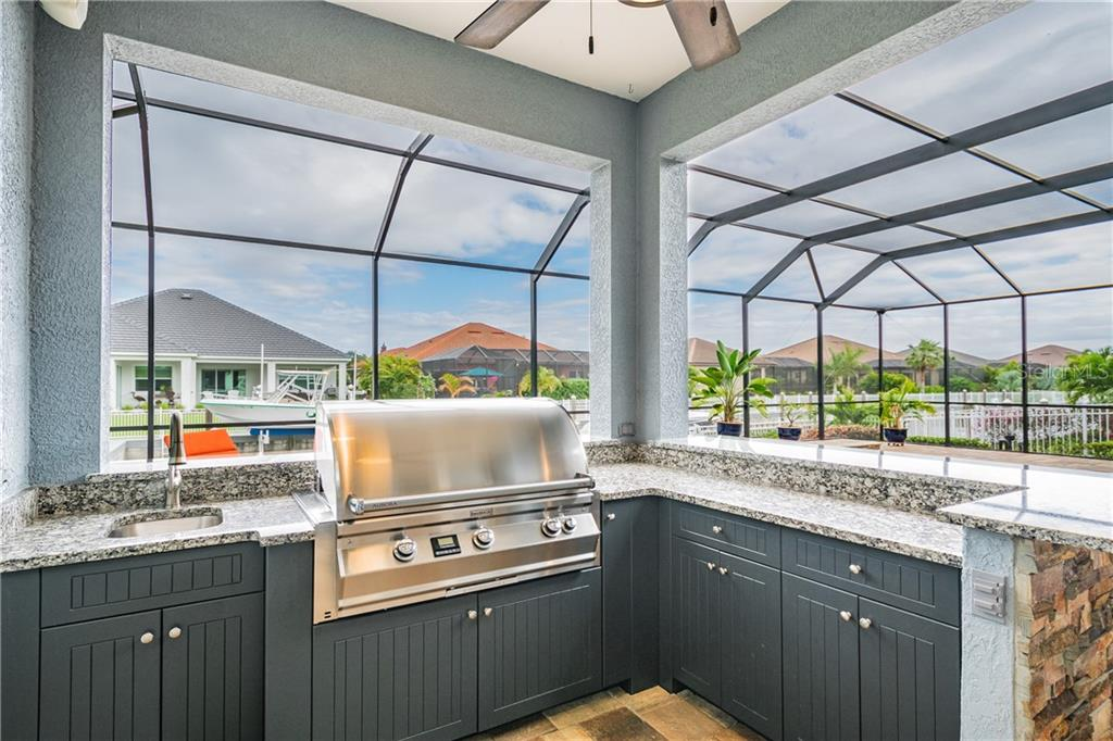 Beautiful outdoor summer kitchen with granite, matching stone to the pool and weather proof cabinetry - Single Family Home for sale at 595 Fore Dr, Bradenton, FL 34208 - MLS Number is A4428657