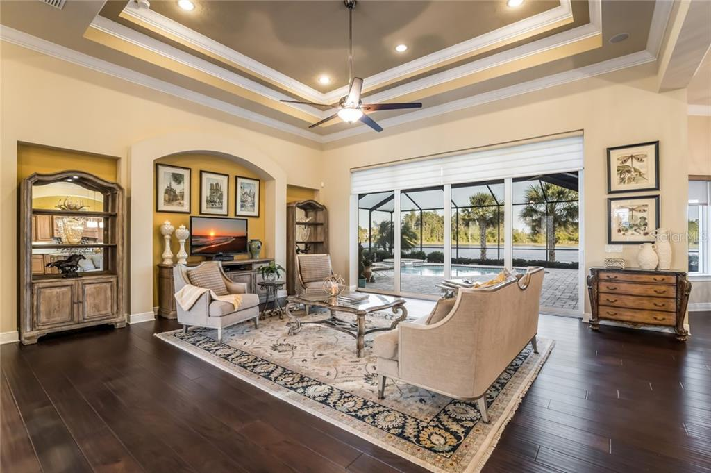 The 10 foot sliders in the living room have 3M protective film with Hunter Douglas shades. - Single Family Home for sale at 19432 Newlane Pl, Bradenton, FL 34202 - MLS Number is A4432094