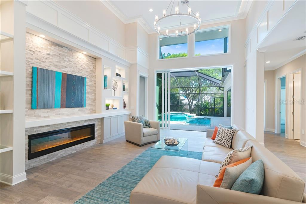 Great room with natural lighting, built-in features and shelving, decorative electric fire place, high ceilings, hardwood flooring - Single Family Home for sale at 1555 Sandpiper Ln, Sarasota, FL 34239 - MLS Number is A4436047