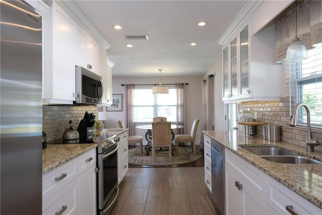 Exquisitely updated kitchen with stone counters and backsplash.  Stainless appliances and modern tile floor. White wood shaker style cabinets with soft close drawers provide amazing storage. - Single Family Home for sale at 2209 Shawnee St, Sarasota, FL 34231 - MLS Number is A4436751