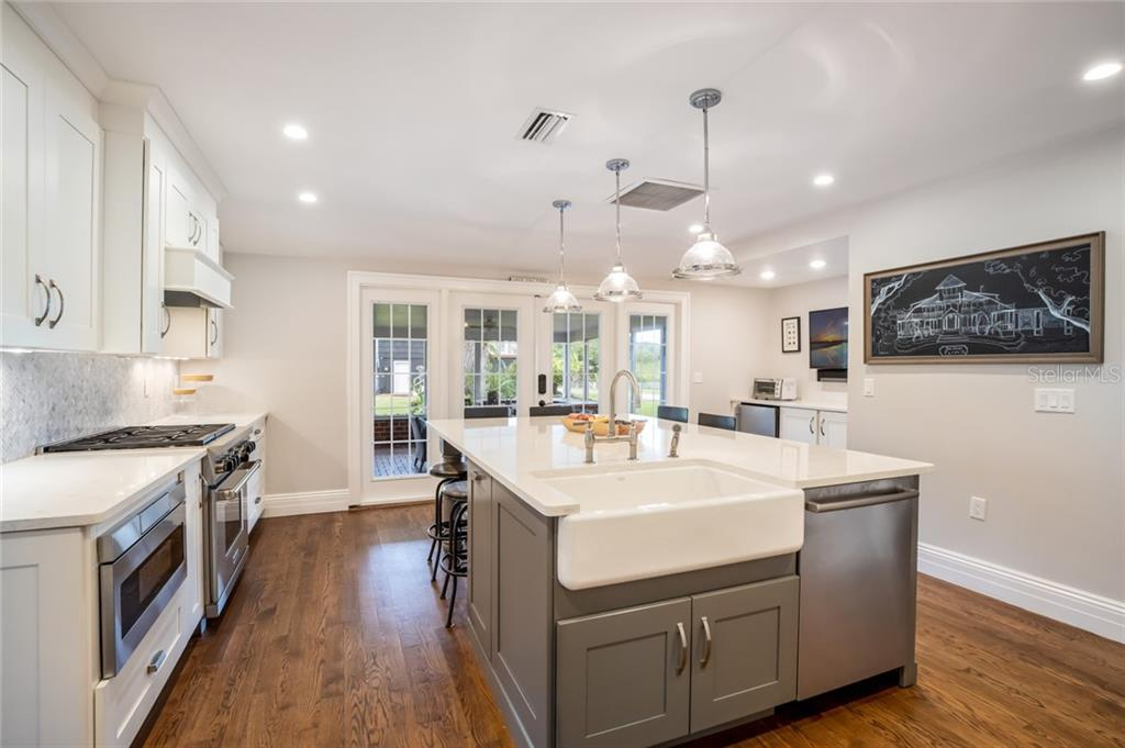 Kitchen features farmhouse sink, wood floors. View looking toward French doors that lead to outdoor screened porch. - Single Family Home for sale at 590 Bayshore Dr, Terra Ceia, FL 34250 - MLS Number is A4437024