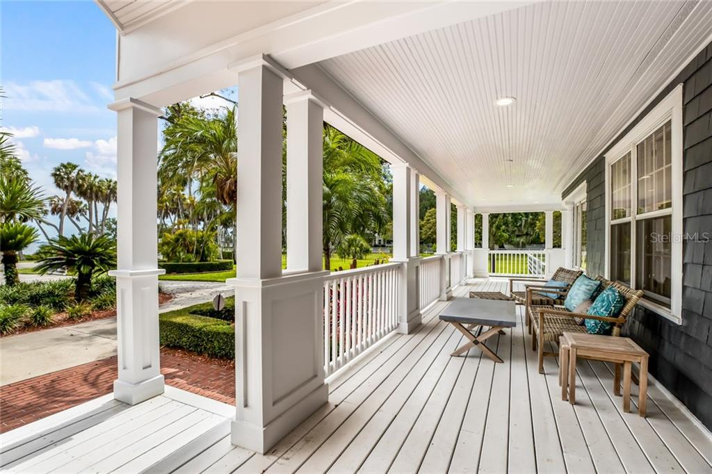 Welcoming wrap-around front porch, perfect spot to watch the sunsets! - Single Family Home for sale at 590 Bayshore Dr, Terra Ceia, FL 34250 - MLS Number is A4437024