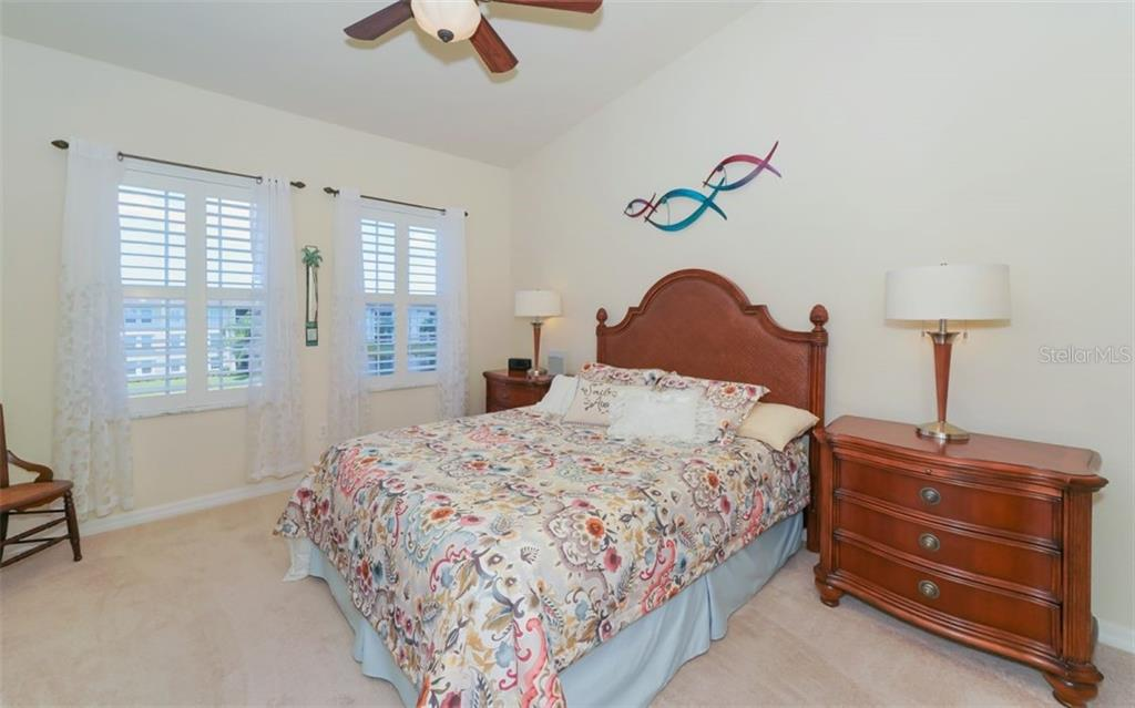 Master bedroom with volume ceilings and plantation shutters on windows overlooking pond. - Condo for sale at 200 San Lino Cir #233, Venice, FL 34292 - MLS Number is A4440138