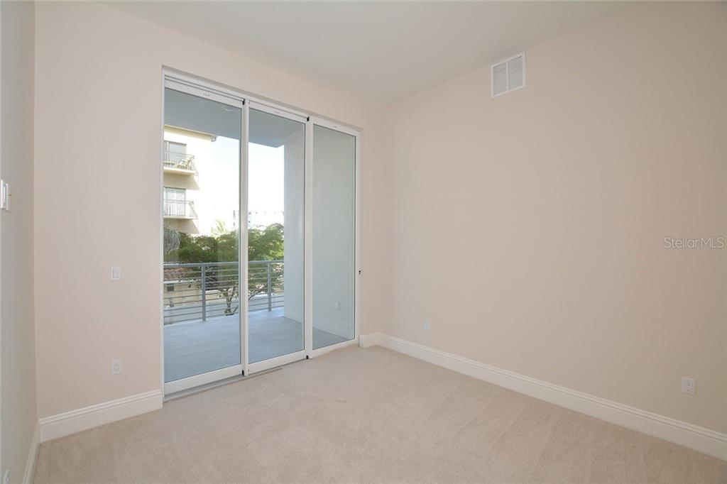 Bedroom 3 with terrace and en-suite bath. - Condo for sale at 609 Golden Gate Pt #202, Sarasota, FL 34236 - MLS Number is A4441802