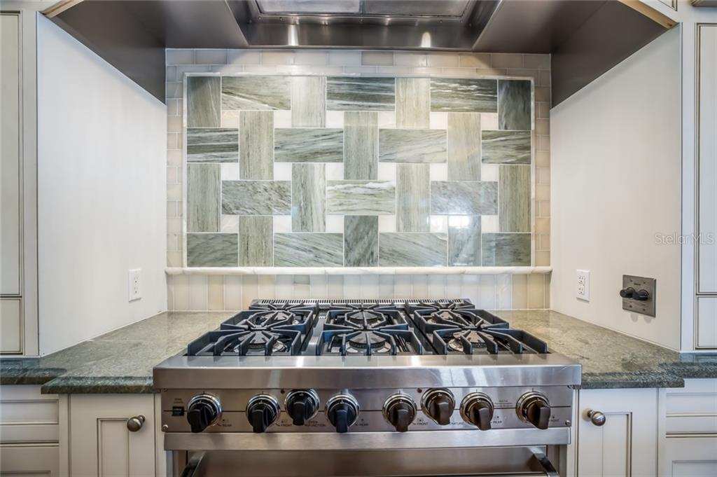 Viking six burner gas range and oven with custom focal point backsplash, a work of art comprised of green and cream alabaster tile laid in a classic basketweave pattern. - Single Family Home for sale at 1522 N Lake Shore Dr, Sarasota, FL 34231 - MLS Number is A4442286