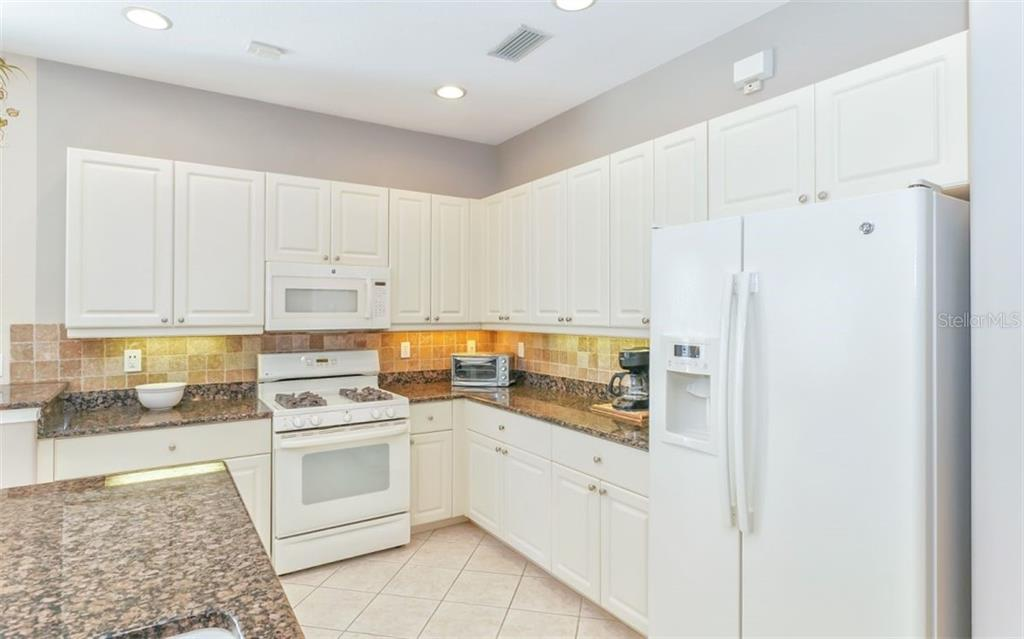 Tumbled tile backsplash and undermount lighting. - Single Family Home for sale at 114 Padova Way #52, North Venice, FL 34275 - MLS Number is A4442496