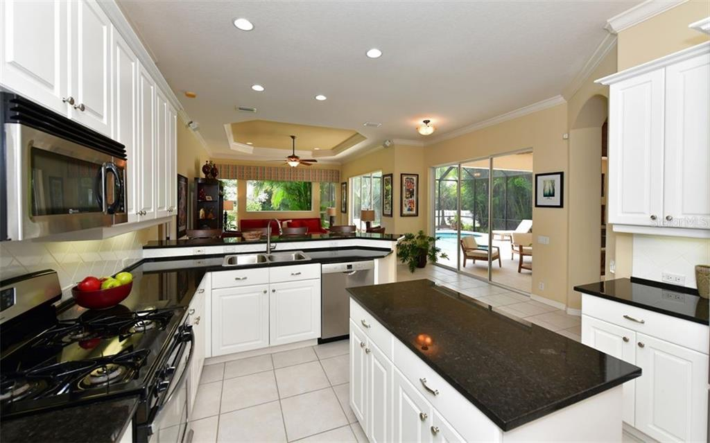 Impressive master suite with tray ceilings, large windows, patio access, and his and her closets. - Single Family Home for sale at 13022 Peregrin Cir, Bradenton, FL 34212 - MLS Number is A4444939