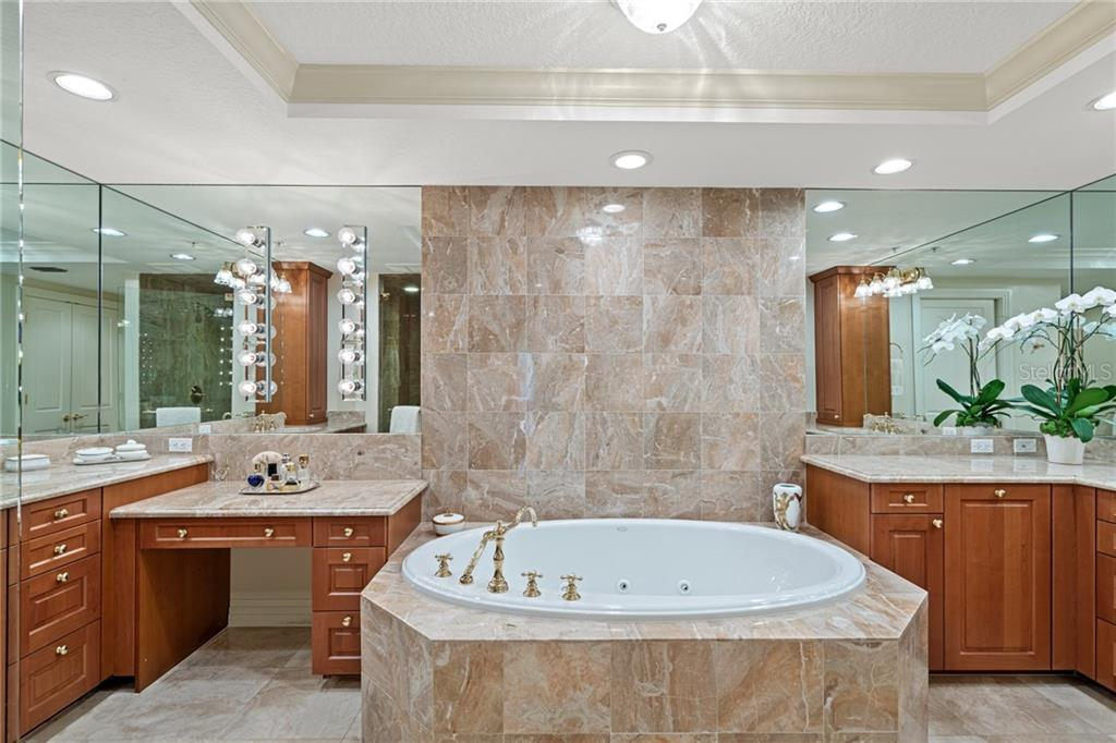 Master bath features: Travertine tile surround, large jetted Kohler soaking tub, dual sinks with his & her split design, glass enclosed shower & private toilet closet. - Condo for sale at 401 S Palm Ave #402, Sarasota, FL 34236 - MLS Number is A4446224