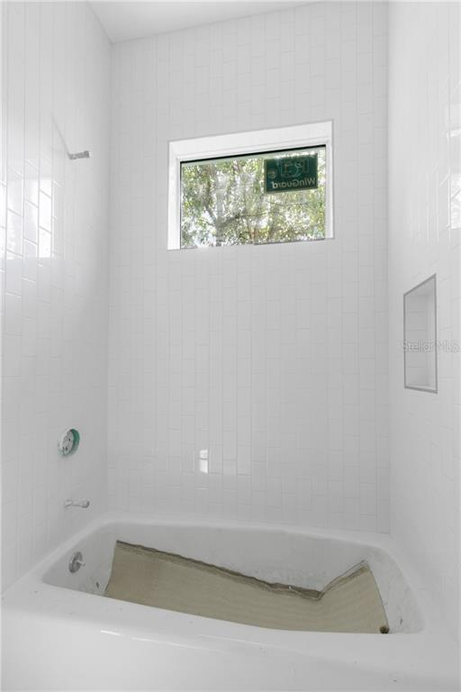 Guest Bathroom 2 shower with tub located between the two guest rooms. - Single Family Home for sale at 1762 Fortuna St, Sarasota, FL 34239 - MLS Number is A4450305