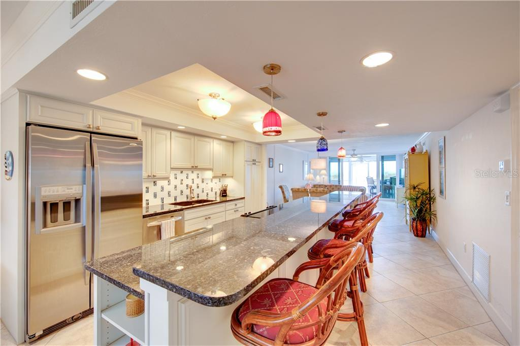 The opened up, fully remodeled kitchen with bar-height counter is ideal for entertaining. - Condo for sale at 555 The Esplanade N #102, Venice, FL 34285 - MLS Number is A4450635