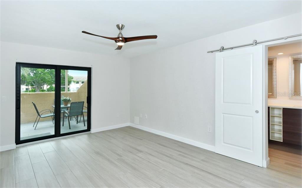 Master bedroom with barn door - Condo for sale at 5217 Heron Way #102, Sarasota, FL 34231 - MLS Number is A4451295