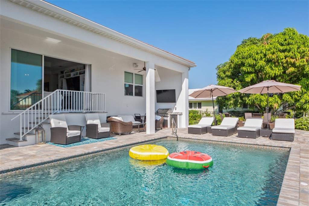 Covered patio with outdoor kitchen and large pool, spa, deck, and dining area. - Single Family Home for sale at 560 Wedge Ln, Longboat Key, FL 34228 - MLS Number is A4452288