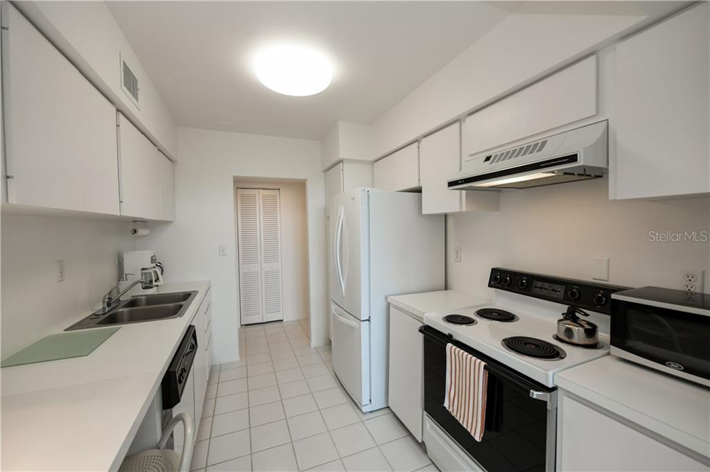 Galley Kitchen with Raised Ceiling, Pantry, and Breakfast Bar. - Condo for sale at 1050 Longboat Club Rd #803, Longboat Key, FL 34228 - MLS Number is A4454175