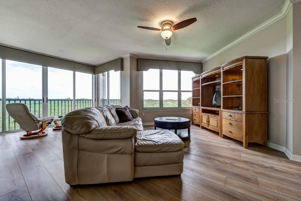 The spacious great room has crown moulding and large windows framing the lovely views of the mangroves below. - Condo for sale at 5420 Eagles Point Cir #204, Sarasota, FL 34231 - MLS Number is A4454318