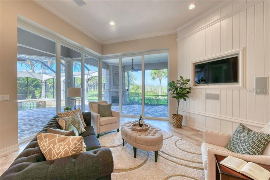 View of family room pocket sliders with view onto lanai and gas fireplace - Single Family Home for sale at 3719 Founders Club Dr, Sarasota, FL 34240 - MLS Number is A4455099