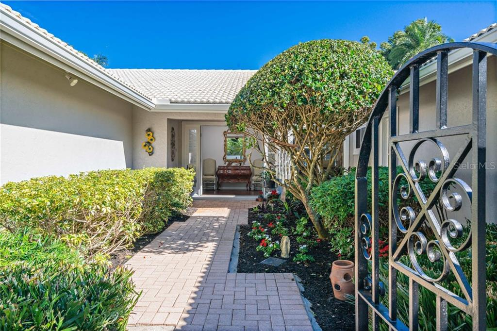 Beautifully landscaped walkway and courtyard to front entry. - Single Family Home for sale at 4557 Camino Real, Sarasota, FL 34231 - MLS Number is A4457740