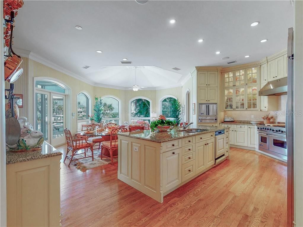 The designer kitchen opens to the sunroom with loads of space for a casual dining table. - Single Family Home for sale at 1590 Harbor Sound Dr, Longboat Key, FL 34228 - MLS Number is A4463437