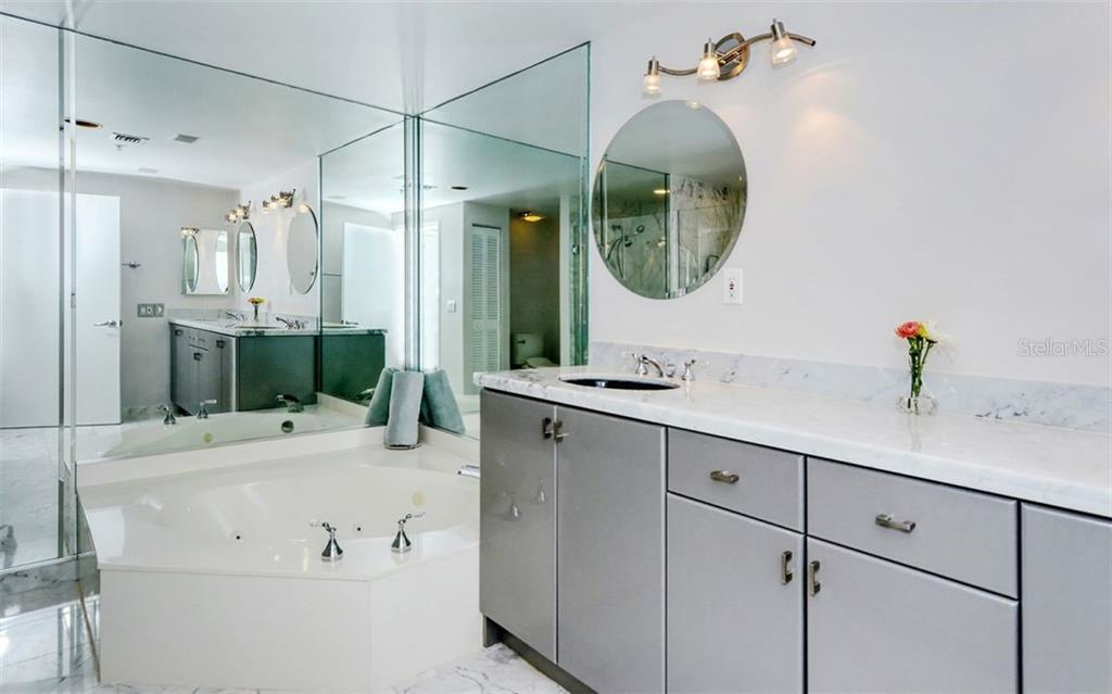 Master bath features soaking tub and dual sinks surrounded by marble shower and flooring. - Condo for sale at 1800 Benjamin Franklin Dr #B1009, Sarasota, FL 34236 - MLS Number is A4463964