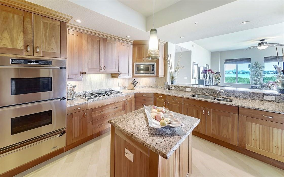 Open kitchen w/ island, double oven and wood flooring - Condo for sale at 1300 Benjamin Franklin Dr #708, Sarasota, FL 34236 - MLS Number is A4471978