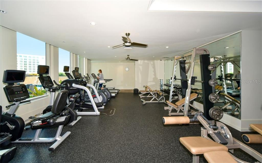 Fitness center overlooks the pool deck - Condo for sale at 1350 Main St #701, Sarasota, FL 34236 - MLS Number is A4472236