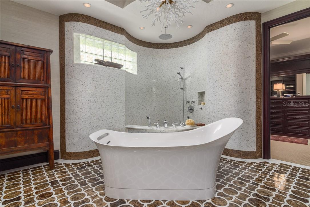Come home to relaxation in your soaking tub in the supersized Zen room with custom marble mosaic tiled flooring and open shower walls with elegant white coral chandelier, rich cabinetry and dual separate vanity areas with backlit glass sinks, two oversized rainshower heads as well as private toilet/bidet space. - Single Family Home for sale at 1807 Oleander St, Sarasota, FL 34239 - MLS Number is A4475067