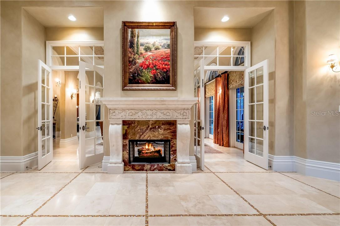 Double Sided Gas Fireplace between Foyer and Gathering Room - Single Family Home for sale at 8499 Lindrick Ln, Bradenton, FL 34202 - MLS Number is A4475594
