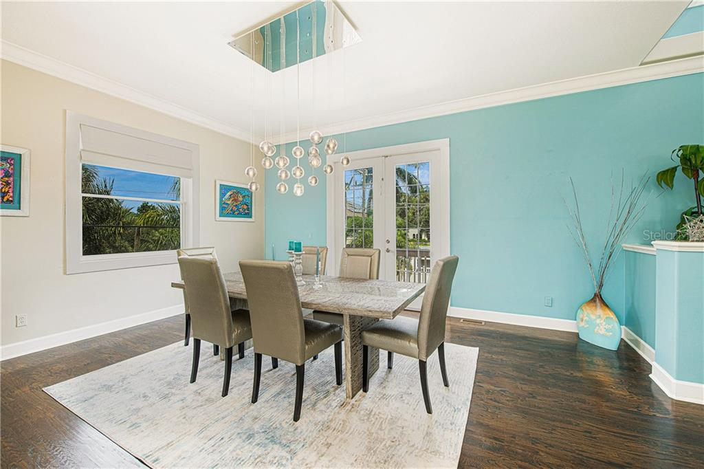 Dining room, with exquisite chandelier and French doors leading to rear deck. - Single Family Home for sale at 7303 Westmoreland Dr, Sarasota, FL 34243 - MLS Number is A4478376
