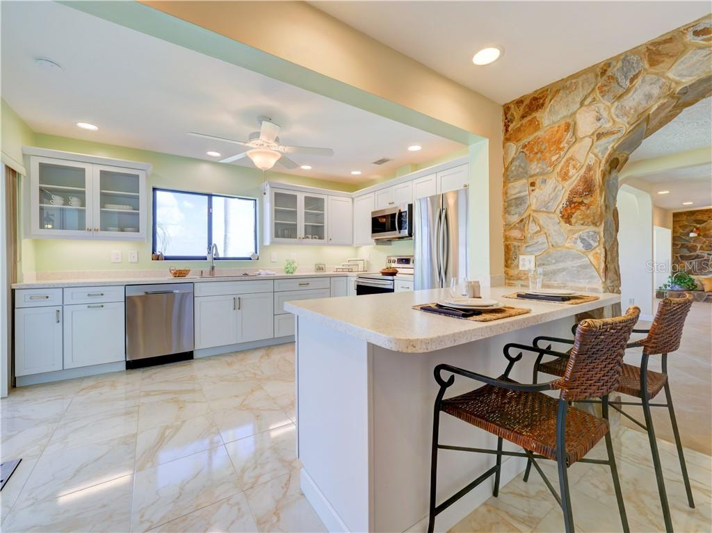 New kitchen with solid surface counter tops, breakfast bar, and brand new stainless steel appliances. - Single Family Home for sale at 2408 Riverside Dr E, Bradenton, FL 34208 - MLS Number is A4480609