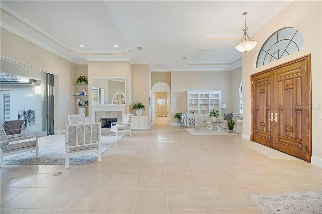 Double solid-wood entry doors open to the formal living room with sliders to the lanai - Single Family Home for sale at 13223 Palmers Creek Ter, Lakewood Ranch, FL 34202 - MLS Number is A4484826