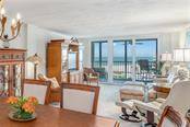 Living room with sliders to covered balcony and views extending out to Gulf of Mexico - Condo for sale at 5880 Midnight Pass Rd #810, Sarasota, FL 34242 - MLS Number is A4208619