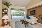 Living Room features a wall of disappearing sliding glass doors opening onto the spacious lanai with heated pool and spa. - Single Family Home for sale at 5585 Siesta Estates Ct, Sarasota, FL 34242 - MLS Number is A4211109