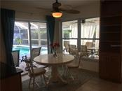Kitchen breakfast nook, with custom cabinet, has sliders that pocket for pool area enjoyment. - Single Family Home for sale at 1611 82nd St Nw, Bradenton, FL 34209 - MLS Number is A4417607