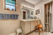 The retro en suite master bath with large walk-in closet that can be accessed from the bath or bedroom areas. - Single Family Home for sale at 1509 Flower Dr, Sarasota, FL 34239 - MLS Number is A4421898