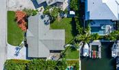 Aerial view of 602 Baronet with canal and boat dock with lift - Single Family Home for sale at 602 Baronet Ln, Holmes Beach, FL 34217 - MLS Number is A4447974