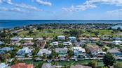 Aerial view of Key Royale Golf Course, Tampa Bay and North Point Harbour in Key Royale - Single Family Home for sale at 609 N Point Dr, Holmes Beach, FL 34217 - MLS Number is A4455659