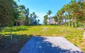 Private driveway off Gulf of Mexico Dr, showing cleared area in the middle of the lot, surrounded by trees - Vacant Land for sale at 5809 Gulf Of Mexico Dr, Longboat Key, FL 34228 - MLS Number is A4460950