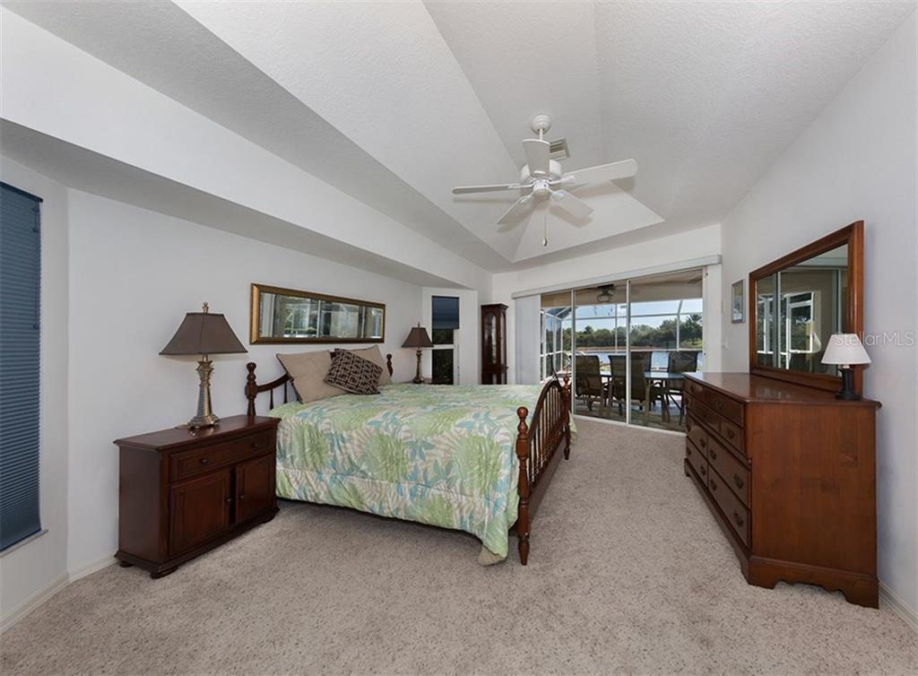 Master bedroom with sliders to lanai/pool - Single Family Home for sale at 866 Wood Sorrel Ln, Venice, FL 34293 - MLS Number is N5915362