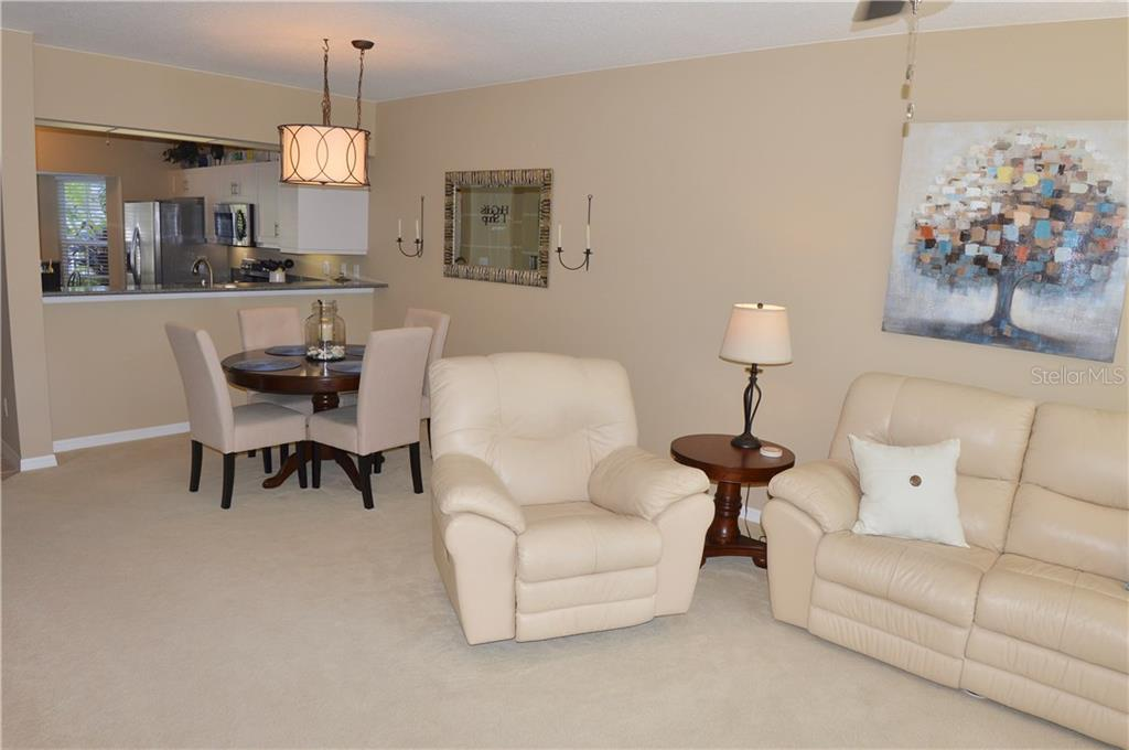 Living room to dining room - Condo for sale at 903 Addington Ct #102, Venice, FL 34293 - MLS Number is N5916962