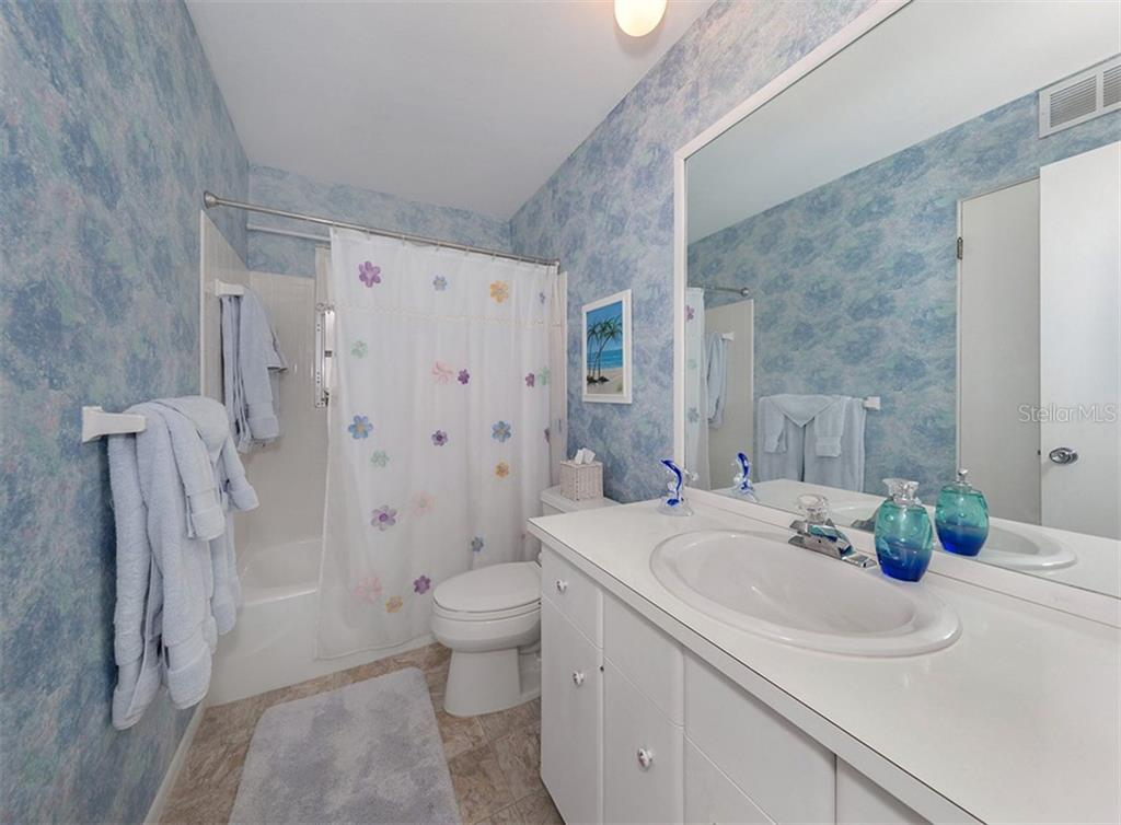 Guest bathroom with tub/shower and a linen closet. - Condo for sale at 100 The Esplanade N #4, Venice, FL 34285 - MLS Number is N6100334