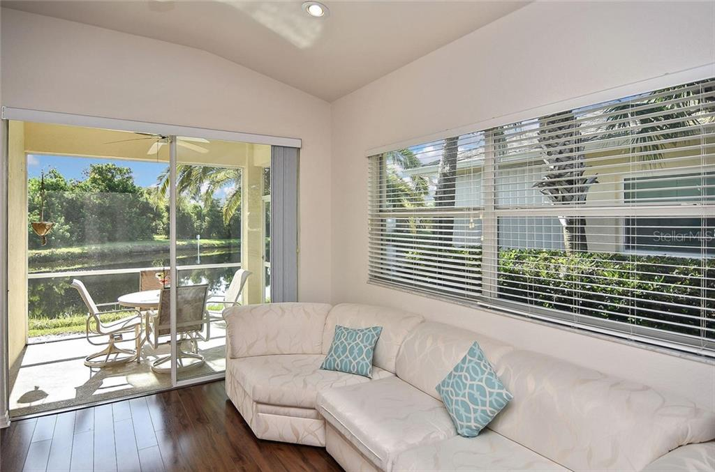 Living room with sliders to lanai - Villa for sale at 1720 Fountain View Cir, Venice, FL 34292 - MLS Number is N6101363